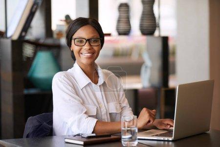 junge erfolgreiche schwarze Frau lächelt in die Kamera, die hinter dem Notizbuch sitzt