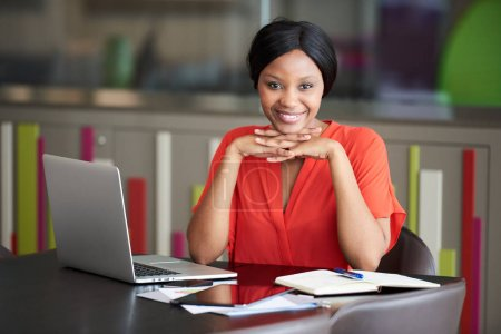 Black businesswoman smiling while supporting her head with her hands