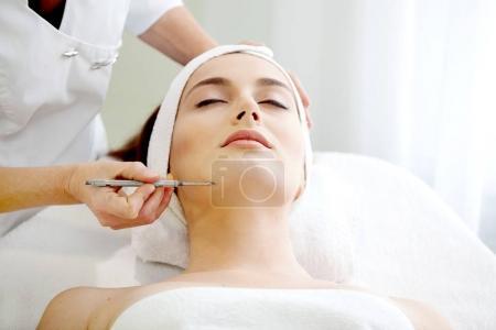 Photo pour Spa de santé : Gros plan de la belle jeune femme relaxante ayant massage du visage (électrolyse), avec orchidée en cheveux longs bruns . - image libre de droit