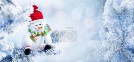 Weihnachtsschneemann hängt an einem Ast