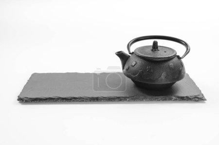 Cast-iron black teapot located on rectangular shale plate