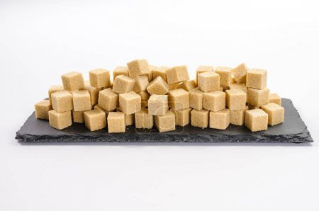 Pile of cane sucar cubes on rectangular dark shale plate
