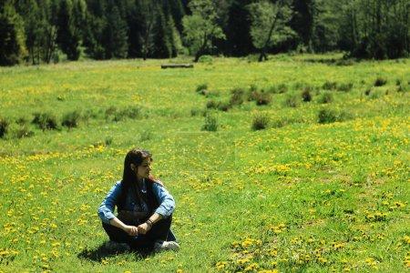 Girl traveler sitting in flower meadow
