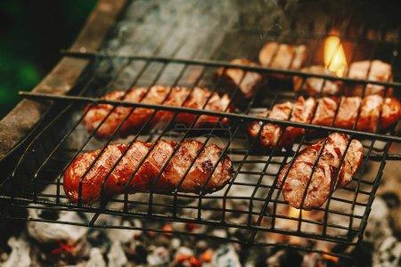 grilled sausages roasting on grates