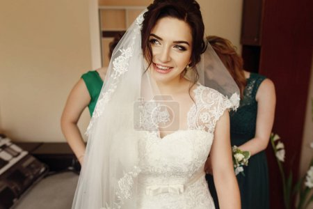 Bridesmaids helping  brunette bride