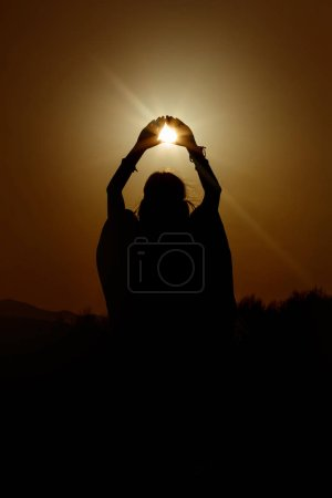 silhouette of woman hands holding sun