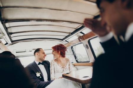 Bride and groom hugging in car