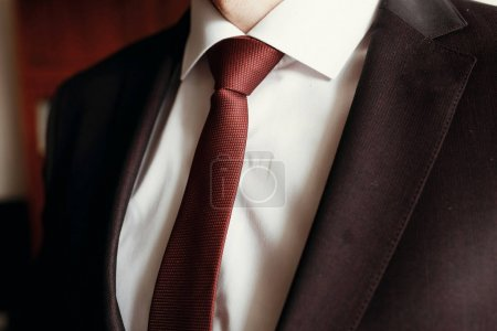 stylish groom in brown suit