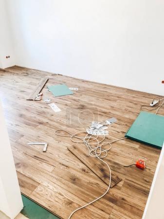 room floor renovation concept. stylish wooden laminate installation, modern white walls.