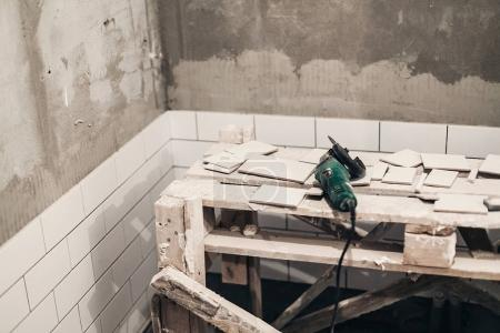 grinder and stylish white tiles for cutting. renovation concept.