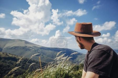 wanderlust and travel concept. stylish traveler man in hat looking at mountains. hipster guy traveling on top of mountains, relaxing at windy grass