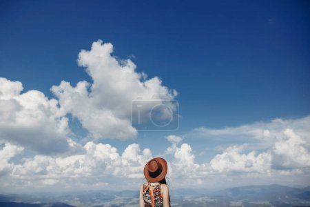 stylish traveler woman in hat looking at sky and mountains. hipster girl on top of mountain, relaxing in the sky and clouds. space for text. atmospheric epic moment. wanderlust and travel concept