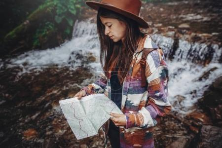 wanderlust and travel concept. stylish traveler girl in hat looking at map, exploring woods. hipster woman with backpack travelling at river in forest. space for text