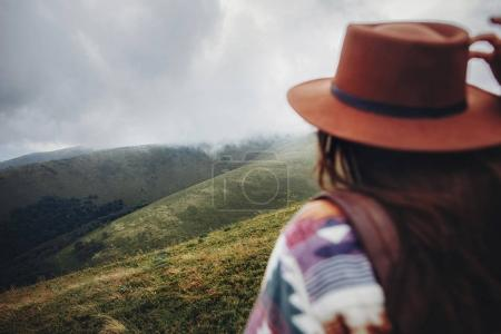 wanderlust and travel concept. girl traveler holding hat and looking at mountains. stylish hipster woman with backpack, focus on mountains in clouds. space for text. atmospheric moment