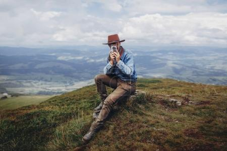 wanderlust and travel concept. man traveler in hat with photo camera sitting on top of mountains. stylish hipster taking photo.