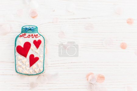 jar with colorful cookie hearts with confetti on white rustic wooden background flat lay. space for text . mock-up. happy mother's day or women's. happy valentine's day greeting card.