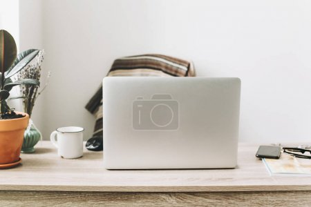 Freelance concept. Desktop with laptop, phone, notebook, coffee cup and plant.