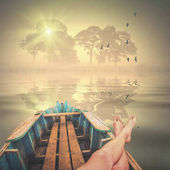Man lays in a boat and enjoy the morning