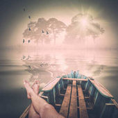 Man lays in a boat and enjoy the morning. Instagram stylization