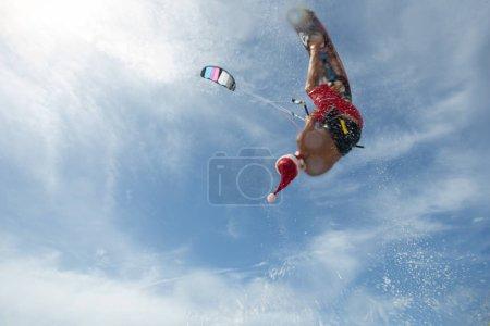 Photo for Christmas Santa Claus Professional kiter riding sea waves on beach - Royalty Free Image