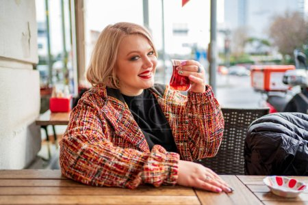 Photo pour Blonde dans un café de rue buvant du thé chaud à table - image libre de droit