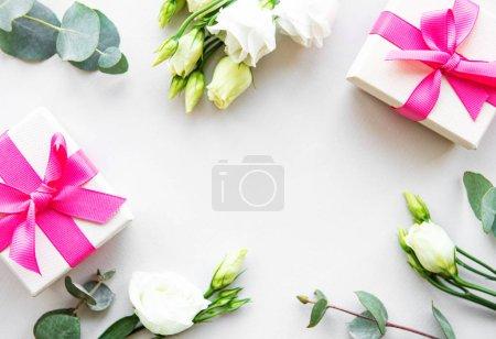 White eustoma  and gift boxes on a white backgroun...