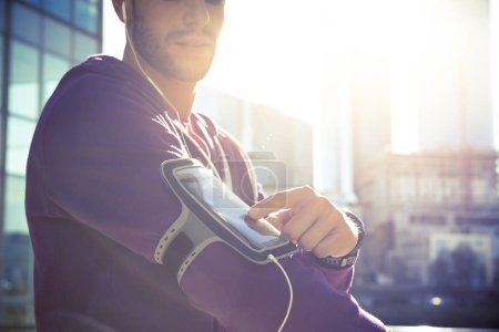 Running workout man listening to music with mp3 player armband o