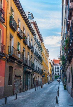 Photo pour Rue tranquille, à Madrid, Espagne. Deux femmes et un enfant à l'extrémité, traversant la voie. De hauts immeubles colorés bordaient la rue avec des trottoirs étroits . - image libre de droit