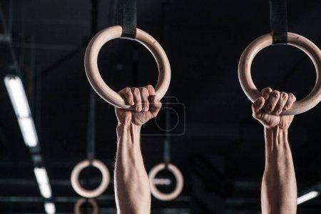Photo pour Jeune athlète masculin avec des anneaux de gymnastique dans le gymnase. se concentrer sur les anneaux - image libre de droit