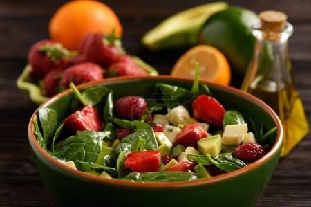 Spinach salad with strawberries, avocado and cheese.