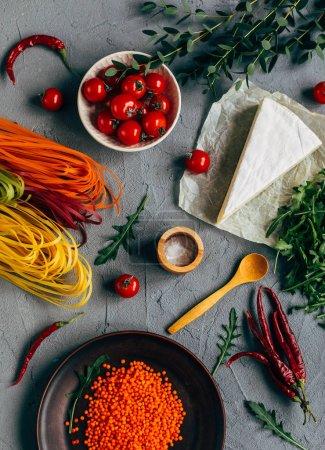 Mesa servida con coloridos espaguetis, trozo de queso, tomates cherry y lentejas en platos sobre fondo gris