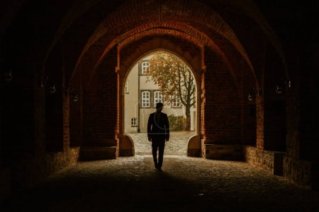man walk in tunnel alone at sunset silhouette.