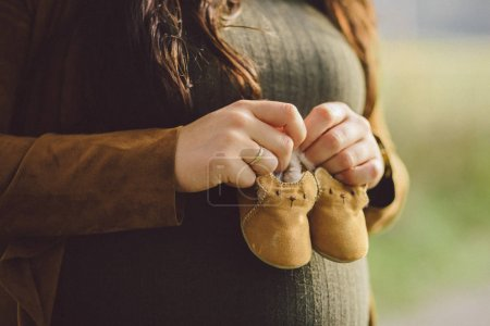 Pregnant woman holding baby booties. Belly with booties close up