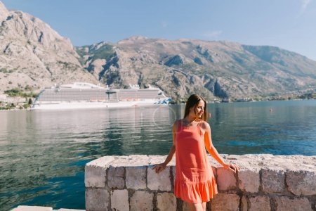 woman sitting on beach with cruise ship view in Montenegro. Kotor bay.