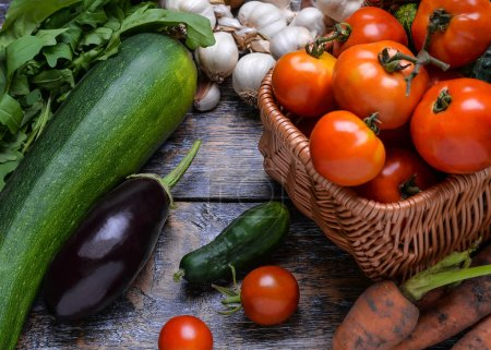 Harvest Vegetables: tomatoes, cucumbers, zucchini, eggplant, onion, garlic, arugula on the wooden background