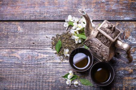 Photo pour Tasse à thé, théière, fleurs de jasmin, thé vert, menthe, sur backgroundd en bois - image libre de droit