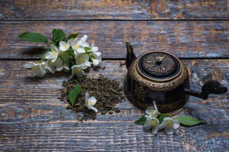 Photo pour Tasse à thé, théière, fleurs de jasmin, thé vert, menthe, sur fond de bois - image libre de droit