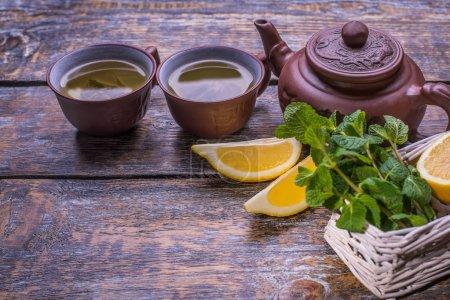 Photo pour Tasse à thé, théière et tranches de citron, gingembre, menthe, thé vert sur fond en bois - image libre de droit