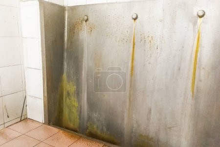 Unhygienic dirty urinal with limescale stain built up