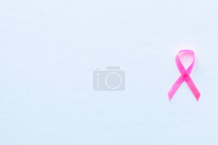 pink ribbon breast cancer symbol on white background and space for text
