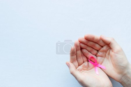 girl holding a pink ribbon as a symbol of breast cancer