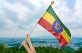 Mladý muž ruce hrdě mává státní vlajka Etiopie na obloze, část 3d vykreslování