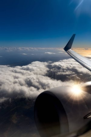 View from window of an airplane during sunset or sunrise. Wing of an airplane flying above the clouds background