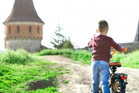 A little boy drives a bicycl