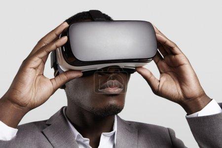 Photo pour Technologie 3d, réalité virtuelle, divertissement, concept de cyberespace. Jeune entrepreneur à la peau foncée utilisant le costume formel utilisant le casque de rift d'oculus avec l'affichage tête-monté, jouant au jeu vidéo dans le bureau - image libre de droit