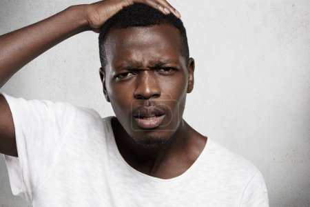 Close up shot of African man wearing white T-shirt holding his head, looking displeased and disappointed with doing something wrong, unhappy with some bad news, frowning with indignant expression