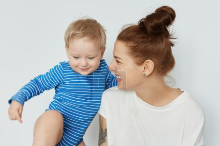 Funny portrait of toddler and happy young mother with bunch of brown hair looking at her tomboy. Young smiling European woman staring at son with enormous love. Positive family lifestyle concept.