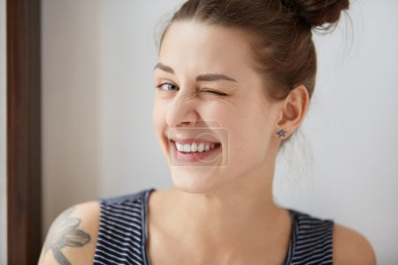 Nice close-up portrait of young European hipster girl with bunch of brown hair and tattoo. Happy tricky cute woman with smiling face blinking at camera in a playful manner. Having fun concept.