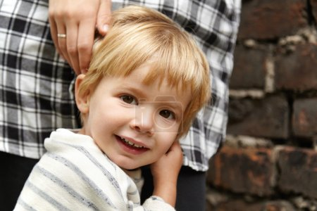 Portrait of happy child walking with mommy in the street. Smiling male kid with brown eyes, blond hair looking at camera. He feels safe because mother standing close to him, ready to protect.
