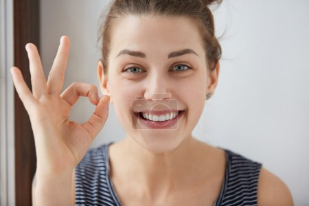 Young European brunette female showing OK-gesture with her fingers. Happy woman in striped top smiling with blue eyes. Her white-teeth mouth and happy face prove everything goes according to plan.